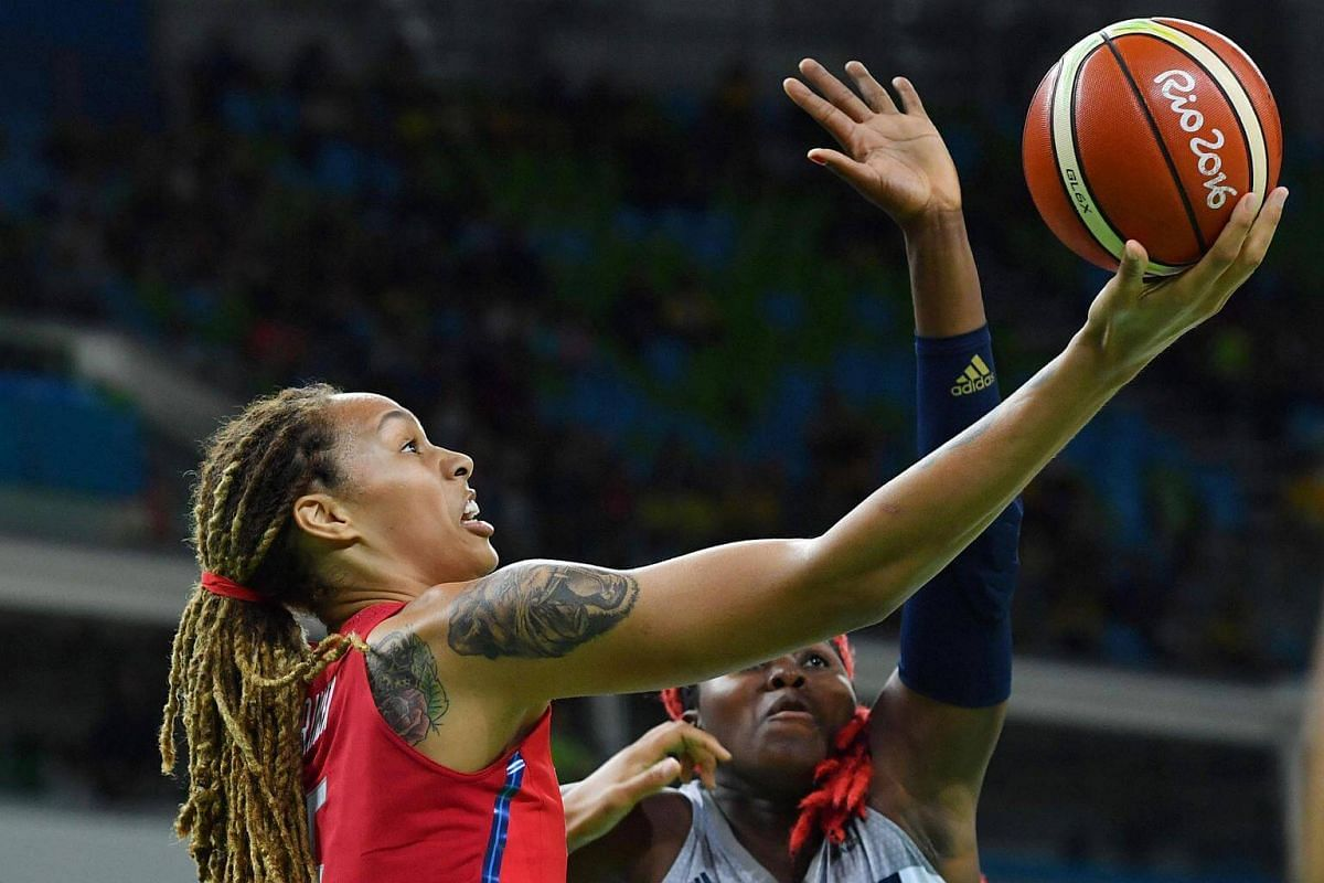 USA's Brittney Griner (left) jumps for a basket with France's Isabelle Yacoubou during a women's semi-final basketball match between France and USA at the Carioca Arena 1.