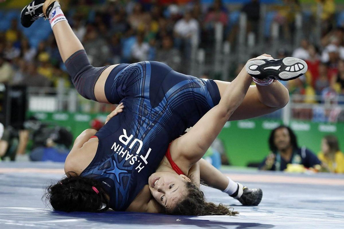 Brazil's Lais Nunes de Oliveira (red) competes with Turkey's Hafize Sahin (blue) during the women's wrestling 63kg qualifications.