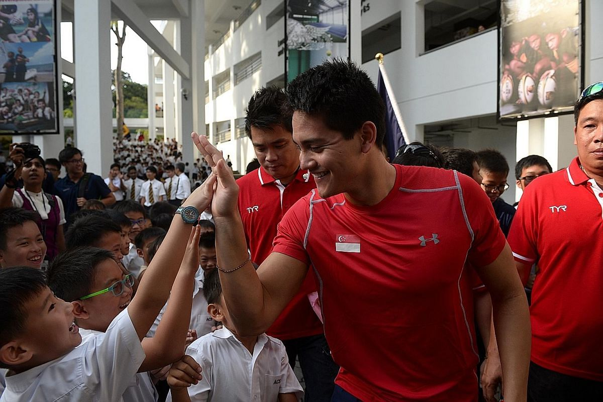 """2012 Olympic gold medallist Chad le Clos advises Schooling not to let people change him. """"Just stay true to yourself, to your family,"""" he says. Schooling giving an Anglo-Chinese School (Junior) pupil a high-five during a visit to the school last week"""