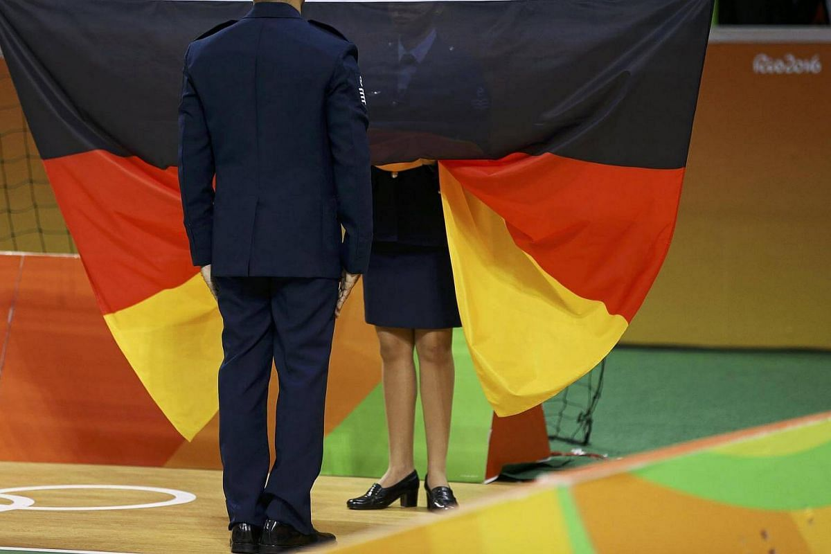 Officials prepare to raise the German flag during the men's handball victory ceremony.