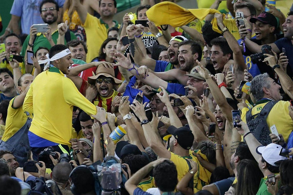 Neymar of Brazil celebrating with fans in the stands after defeating Germany in the Rio 2016 Olympic Games football men's gold medal match.