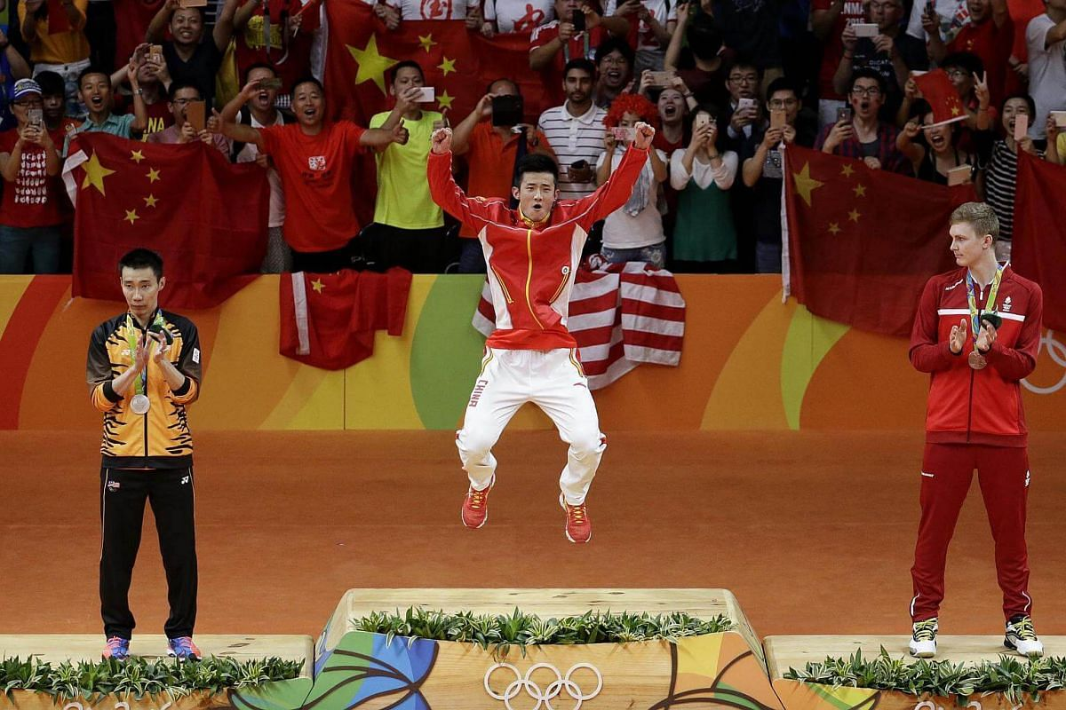 Chen Long (centre) of China jumping onto the podium to receive his gold medal after winning the Rio 2016 Olympic Games badminton men's singles final.