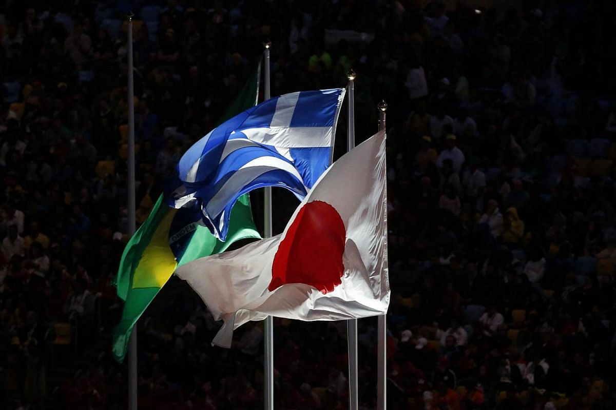 (From left) The flags of Brazil, Greece, and Japan fly high during the closing ceremony of the Rio 2016 Olympic Games on August 21.