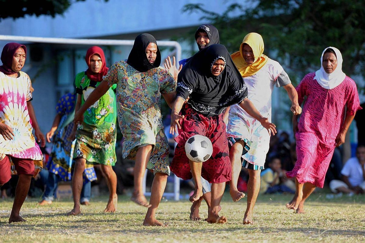 Acehnese men, dressed in women's clothing as an obstacle, play a game of football to mark the 71st Indonesian Independence Day in Banda Aceh.