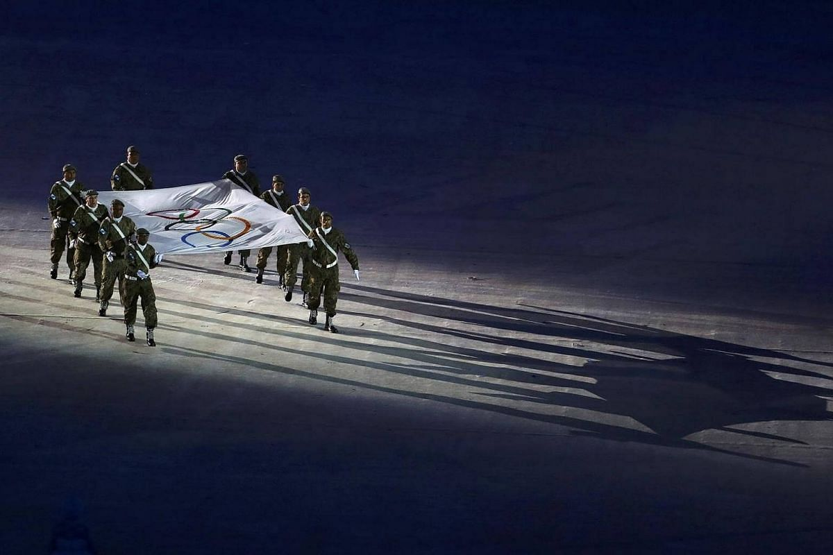 The Olympic Flag is marched in for the flag handover ceremony. The 2020 Olympics will be held in Tokyo, Japan.