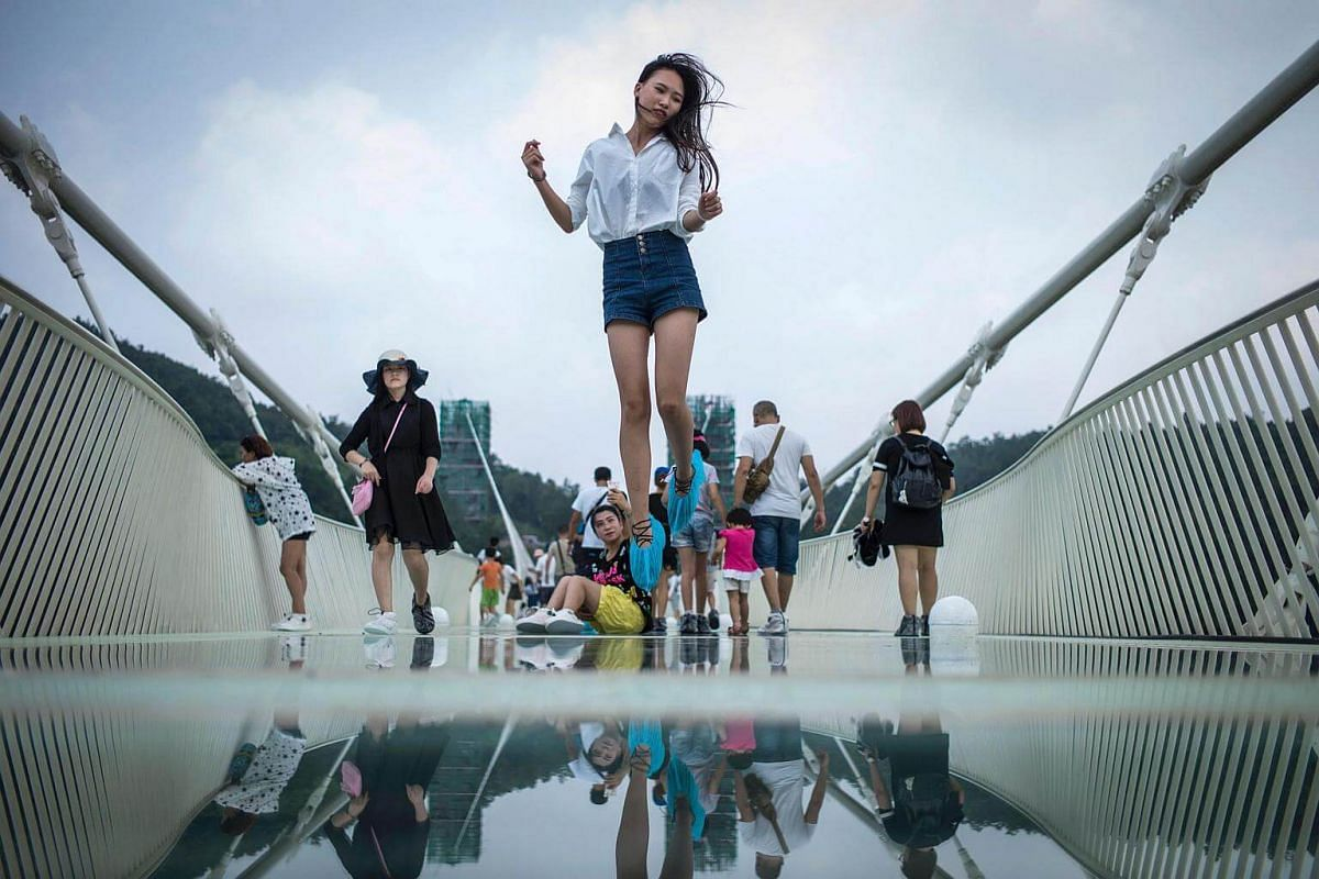 A visitor jumps for a photograph on the world's highest and longest glass-bottomed bridge above a valley in China's Hunan Province on August 21.