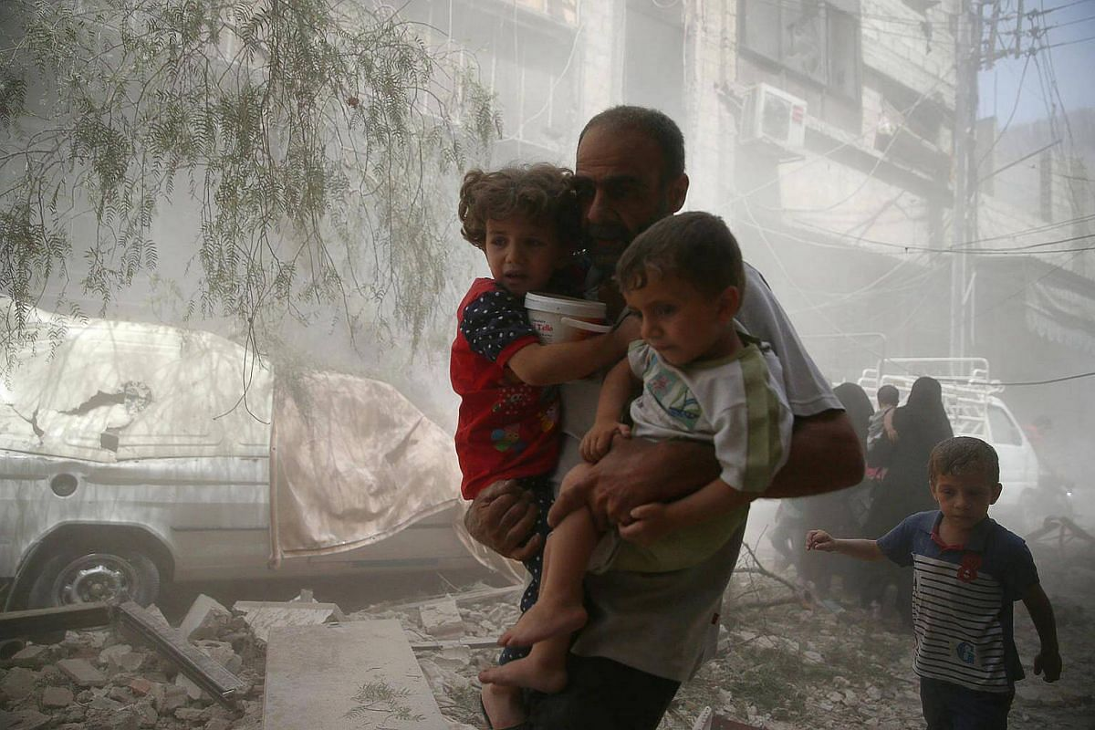 Residents flee a site after an air strike on the rebel-held besieged town of Douma, Syria on August 20.