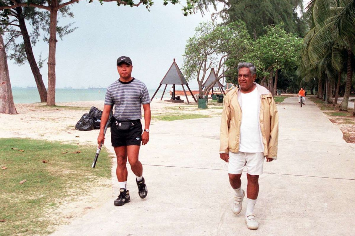 Mr S R Nathan with a bodyguard during a walk at East Coast Park in 2000. Mr Nathan was known for jogging and walking at the park, interacting with people along the way.