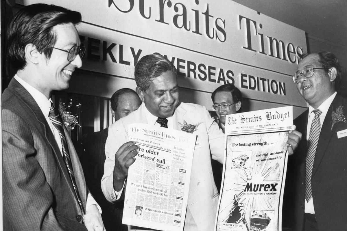 Mr S R Nathan, then Straits Times Press' executive chairman, showing the new weekly overseas edition of The Straits Times and the much older Straits Budget to Mr Philip Yeo (left), chairman of Economic Development Board, in 1987.