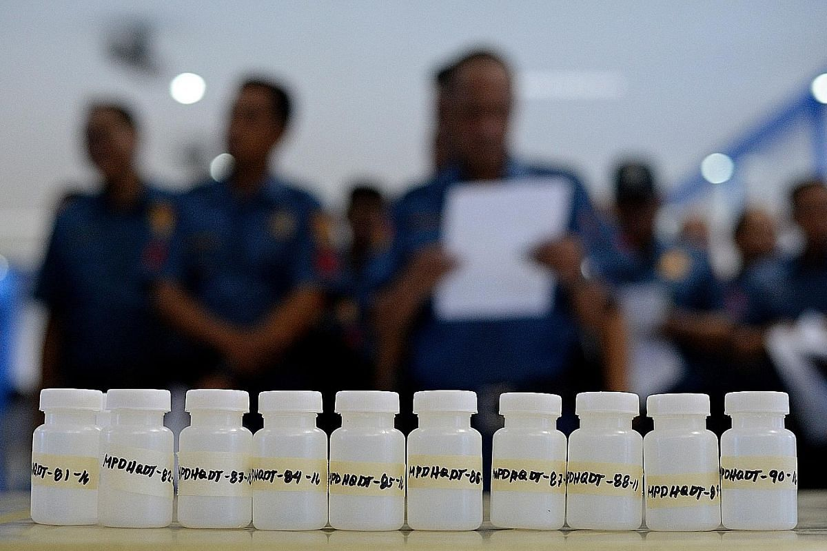 Manila residents behind a police line after a drug bust turned into a deadly gunfight last month. Policemen in Quezon City's Commonwealth district. The number of suspected drug traffickers killed in the ongoing crackdown on drugs has risen to 1,800 s