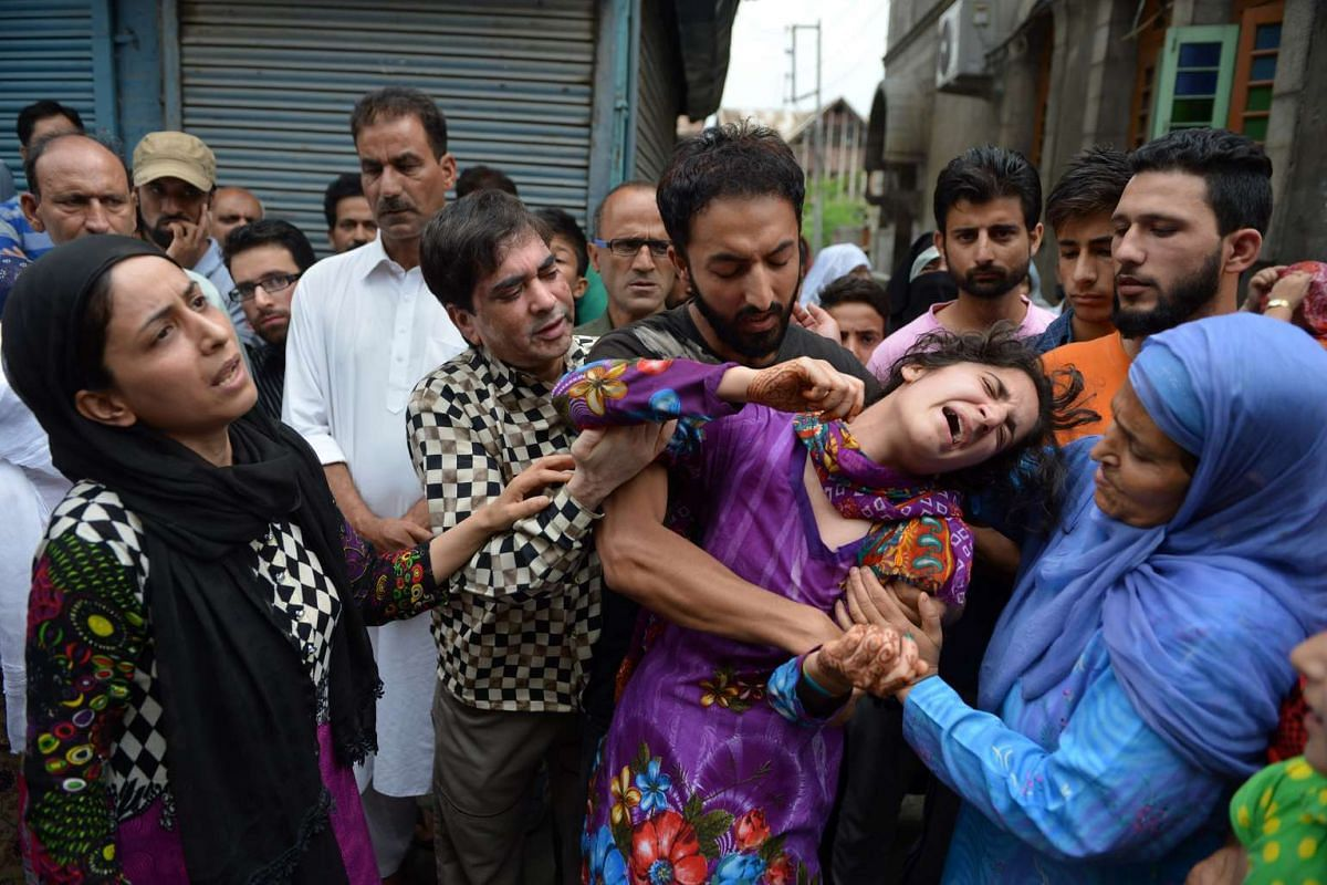 Mahvish (second from right), the sister of Kashmiri Irfan Ahmed, who was killed by a teargas shell, breaks down as local residents visit the family to offer their condolences in Srinagar's Fatah Kadal area on Aug 22, 2016.