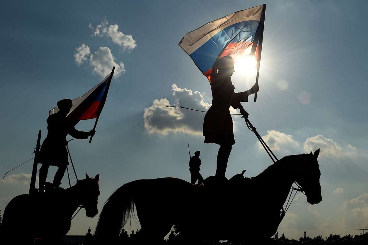 Riders hold the Russian national flag in Moscow on Aug 22, 2016, during celebrations of the National Flag Day.