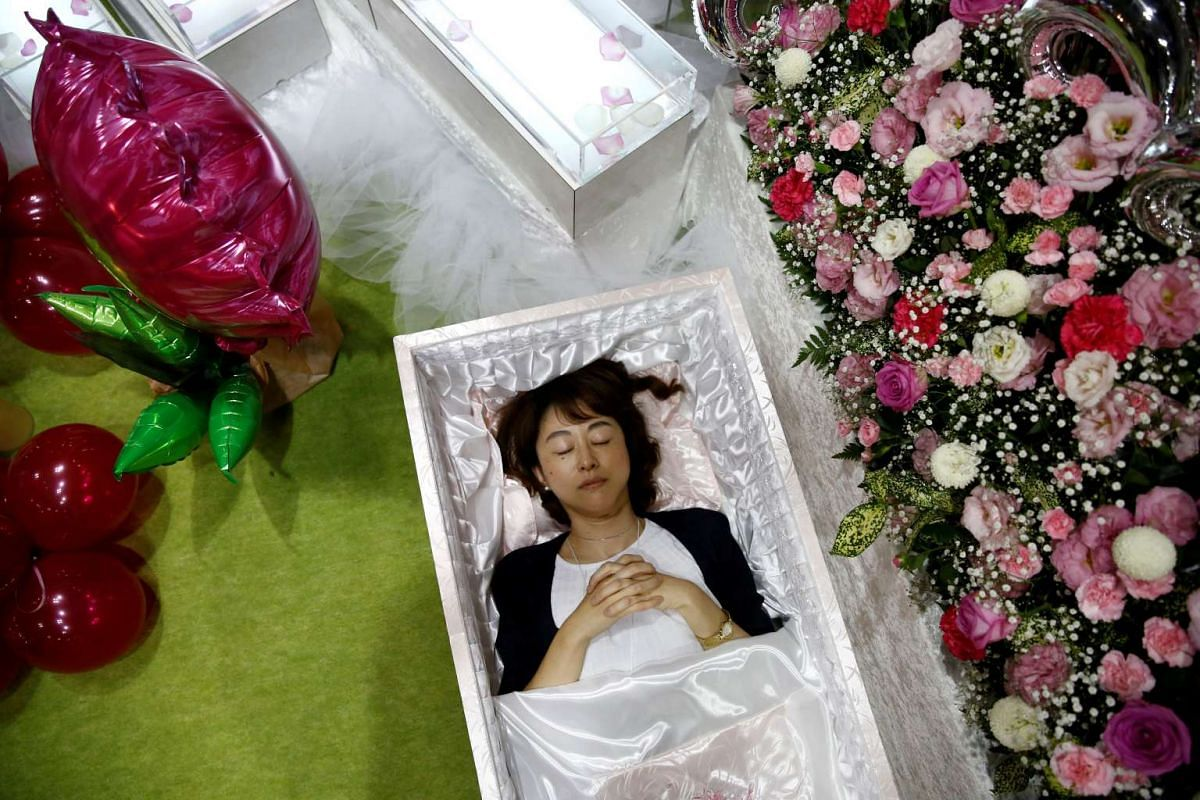 A staff lies in a casket next an altar decorated with flowers and balloons as she demonstrates Okuribito funeral's funeral service at the Life Ending Industry Expo in Tokyo, Japan, on Aug 22, 2016.