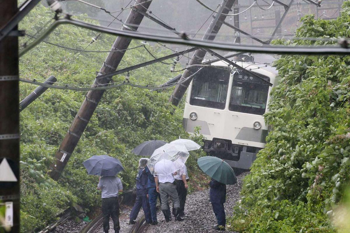 A derailed train in a landslide on the Seibu Tamako line in Higashimurayama, western Tokyo after Typhoon Mindulle struck near Tokyo.