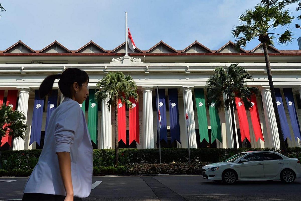 A woman walks past  the Ministry of Health building with a state flag at half-mast as a mark of respect for former president S R Nathan.
