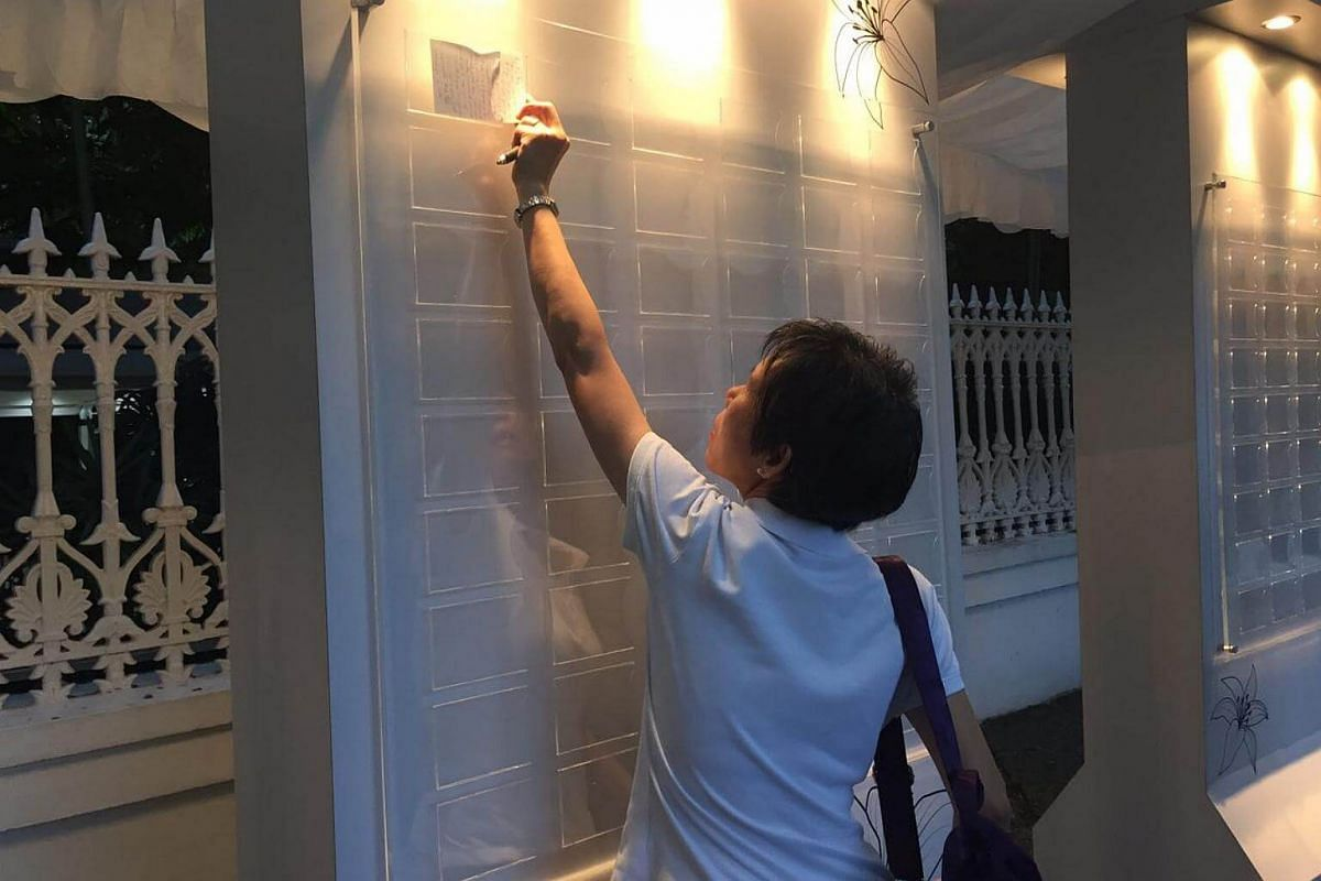 Madam Celin Foong, 53, account executive at the Istana, puts up her condolence message. She had been praying for Mr Nathan since he was admitted to hospital.