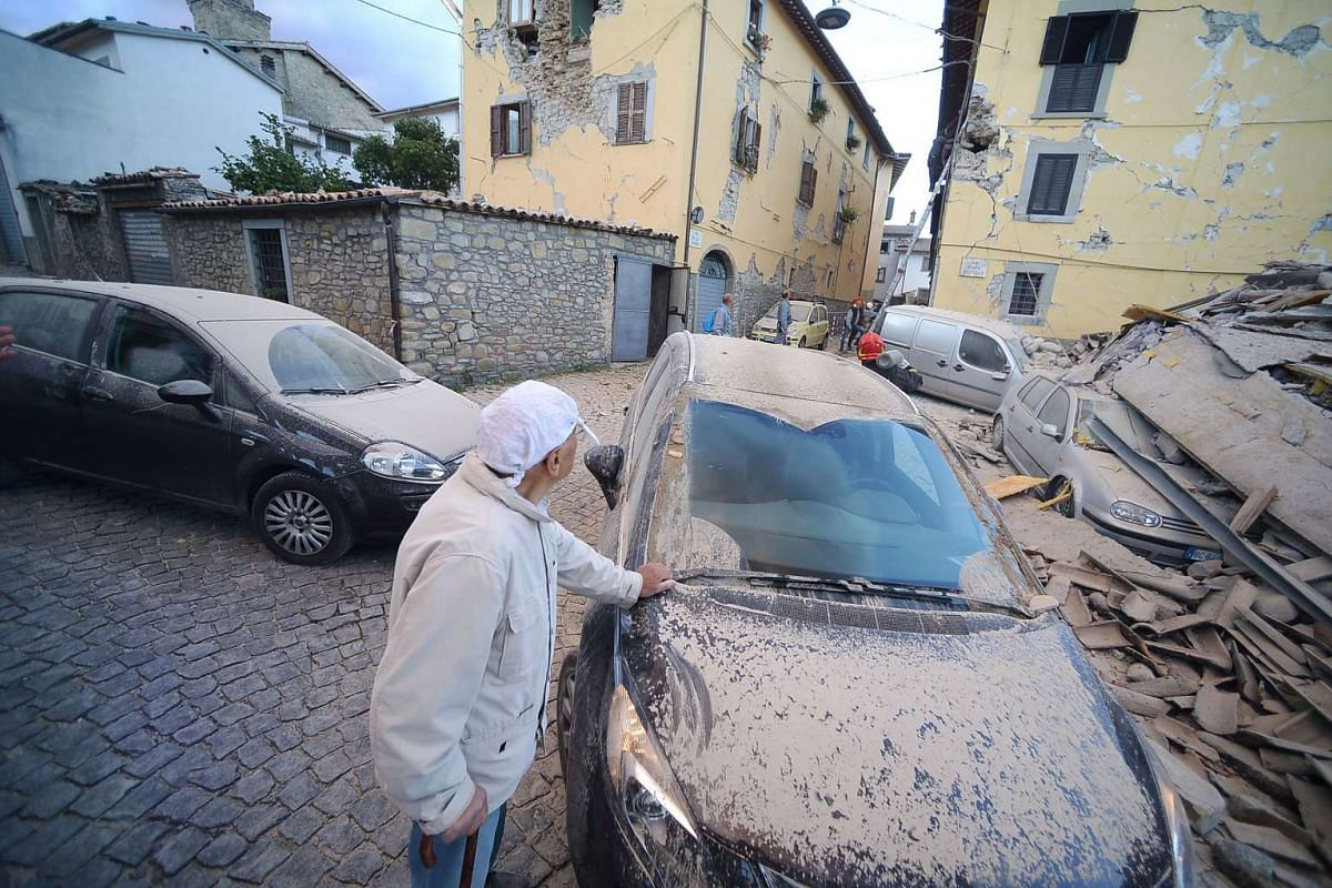 A man looks at damaged buildings after a strong heartquake hit Amatrice, Italy, on Aug 24, 2016.