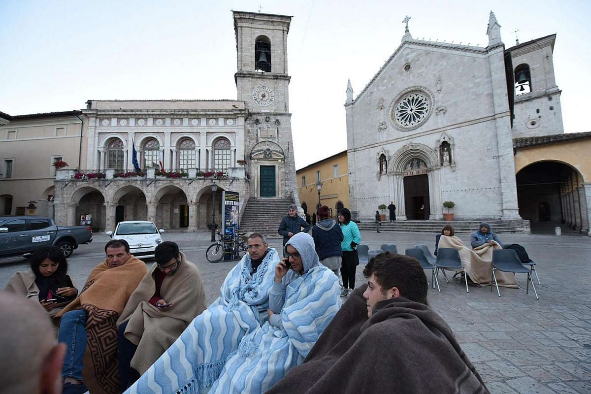 People wait outside after spending the night on a street after an earthquake hit central Italy in Norcia, on Aug 24, 2016.