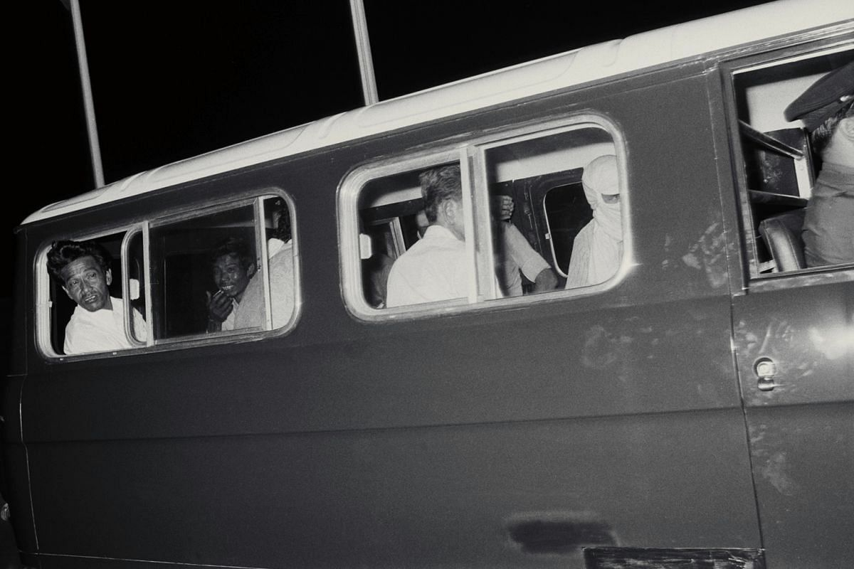 In the police van taking them to the airport, hostages Omar Ahmad (left) and Ulot Idris present contrasting faces. A hijacker (right) cuts a grim figure.