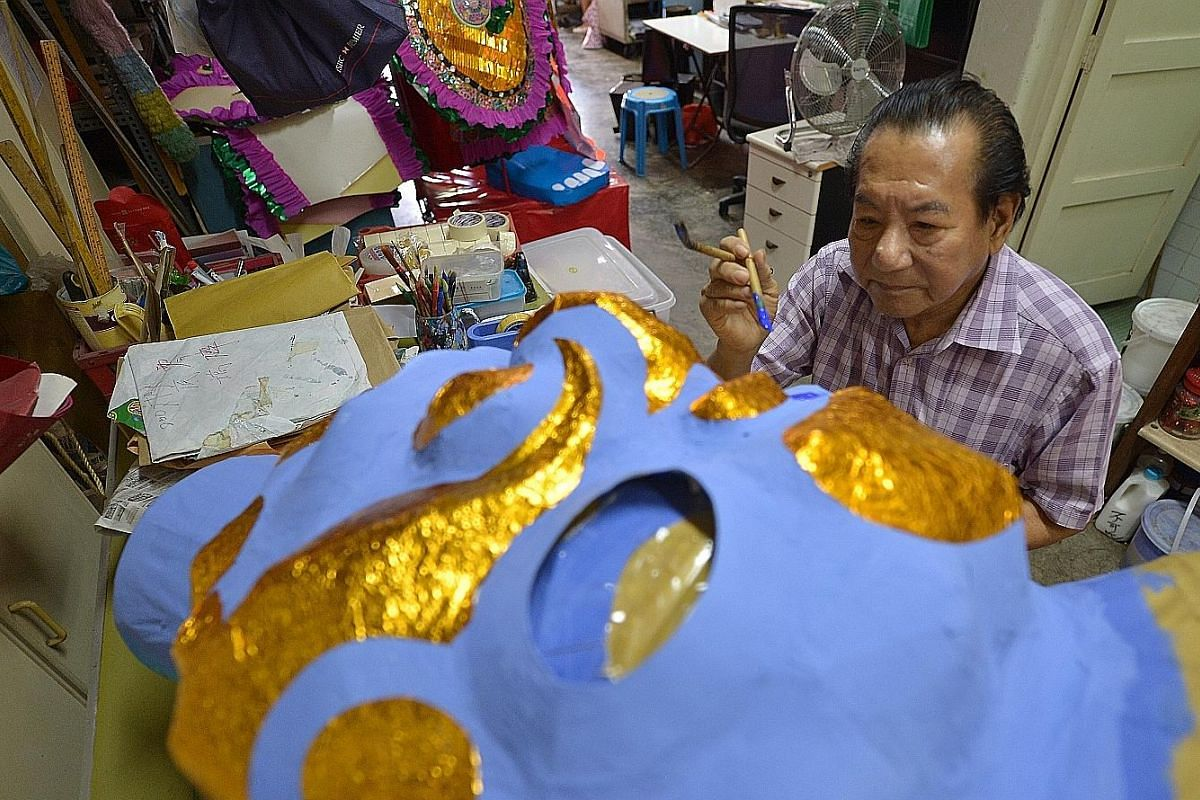 """Priests lead fish merchants through the """"Passing of Lantern"""" ritual which symbolises the passing of blessings to those present as well as the next generation."""
