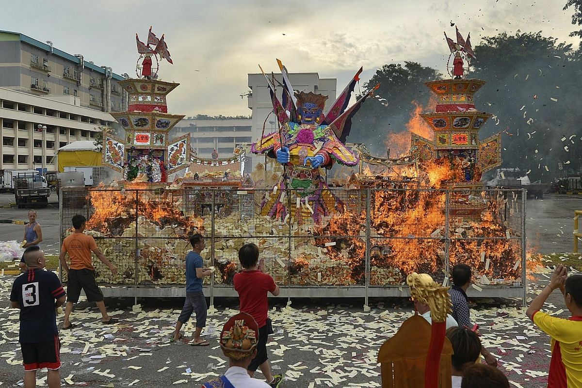 """Fish merchants and their employees toss joss paper into the air while shouting """"huat ah"""" (Hokkien for """"prosper""""), hoping to appease the spirits and bring prosperity to their businesses."""