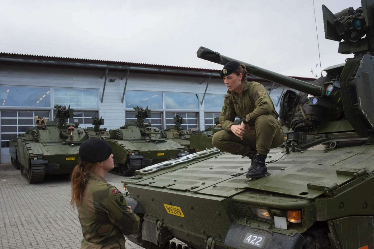 Female soldiers next to a CV90 combat vehicle at the armoured battalion in Setermoen, northern Norway, on Aug 11, 2016.