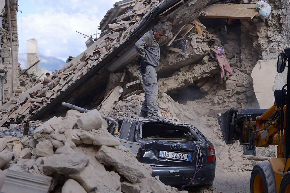 A man stands on top of a damaged car in Amatrice on Aug 24, after a powerful earthquake rocked central Italy.
