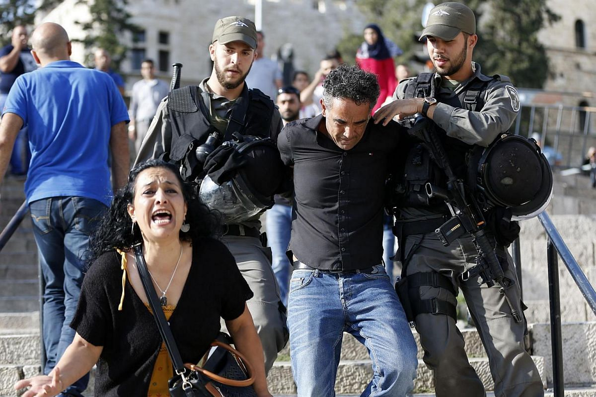 A woman reacts as Israeli border policemen arrest a Palestinian protester during a demonstration against administrative detention and in support of Palestinian prisoner Bilal Kayed on Aug 24 at Damascus Gate, the main entrance to Jerusalem's Old City