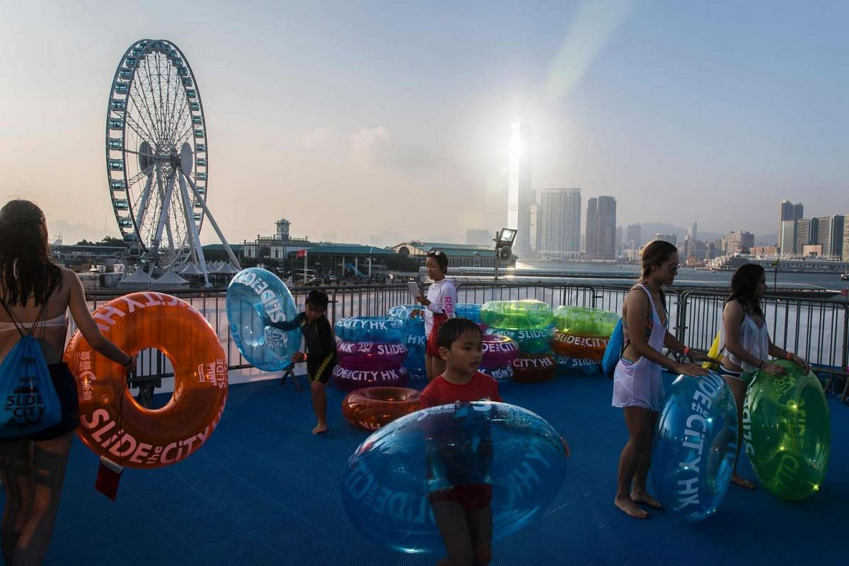 Participants wait with tubes to ride a giant waterslide set up in the Central district of Hong Kong on Aug 25, 2016.