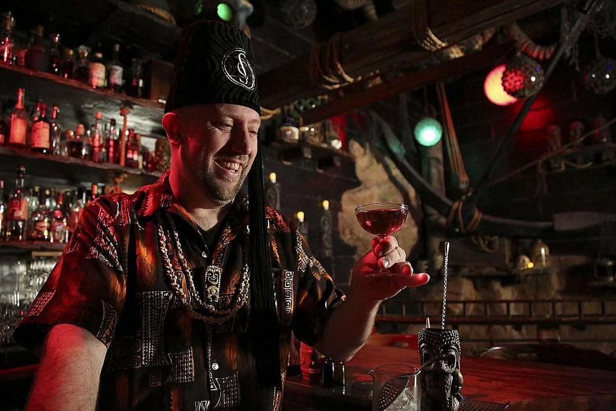 Martin Cate (above), at his bar Smuggler's Cove in San Francisco, has written a book (left) about tiki cocktails with his wife.