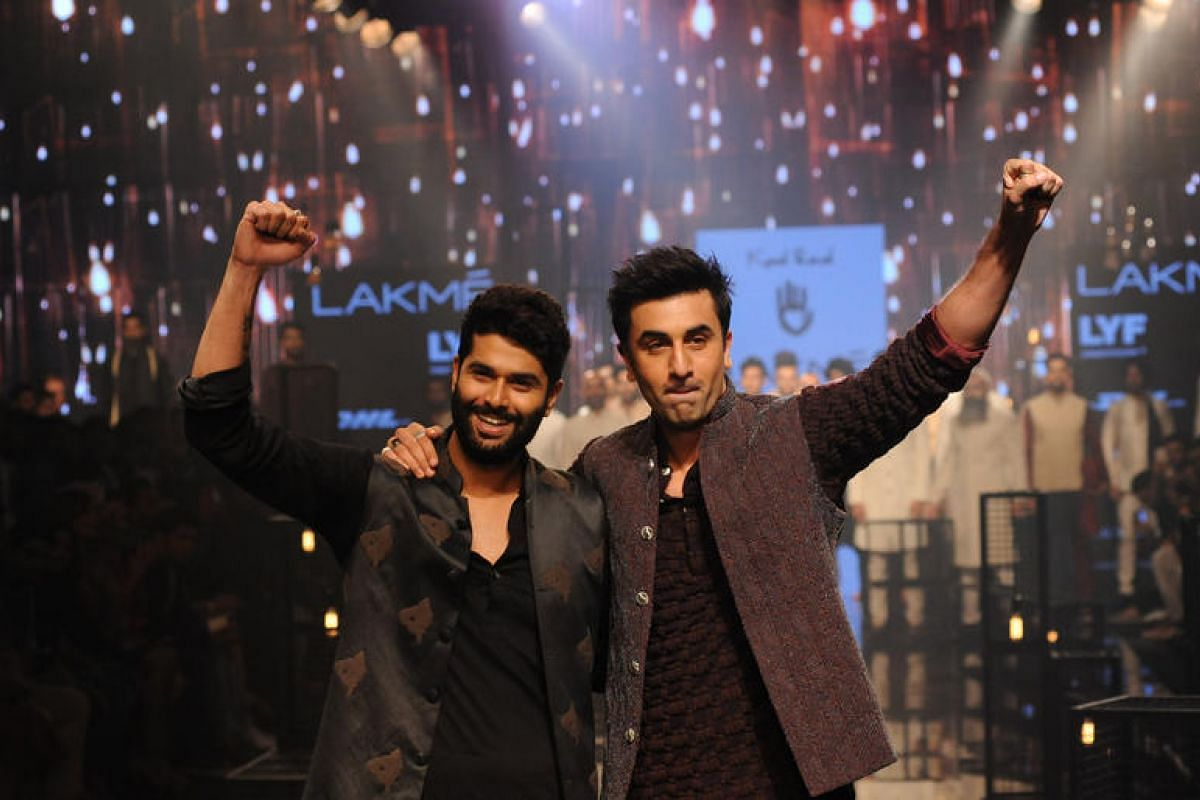 Indian Bollywood actor Ranbir Kapoor (right) showcases a creation by designer Kunal Rawal (left) during the Grand Finale of Lakme Fashion Week in Mumbai, India, on Aug 28.