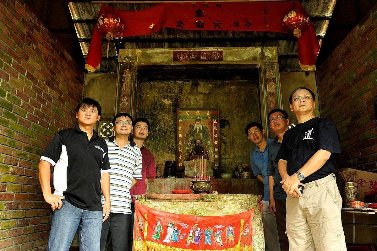 Mr Charles Goh (left) and Mr Raymond Goh (second from left) at the Tu Di Gong temple at Bukit Brown Cemetery in March 2010.