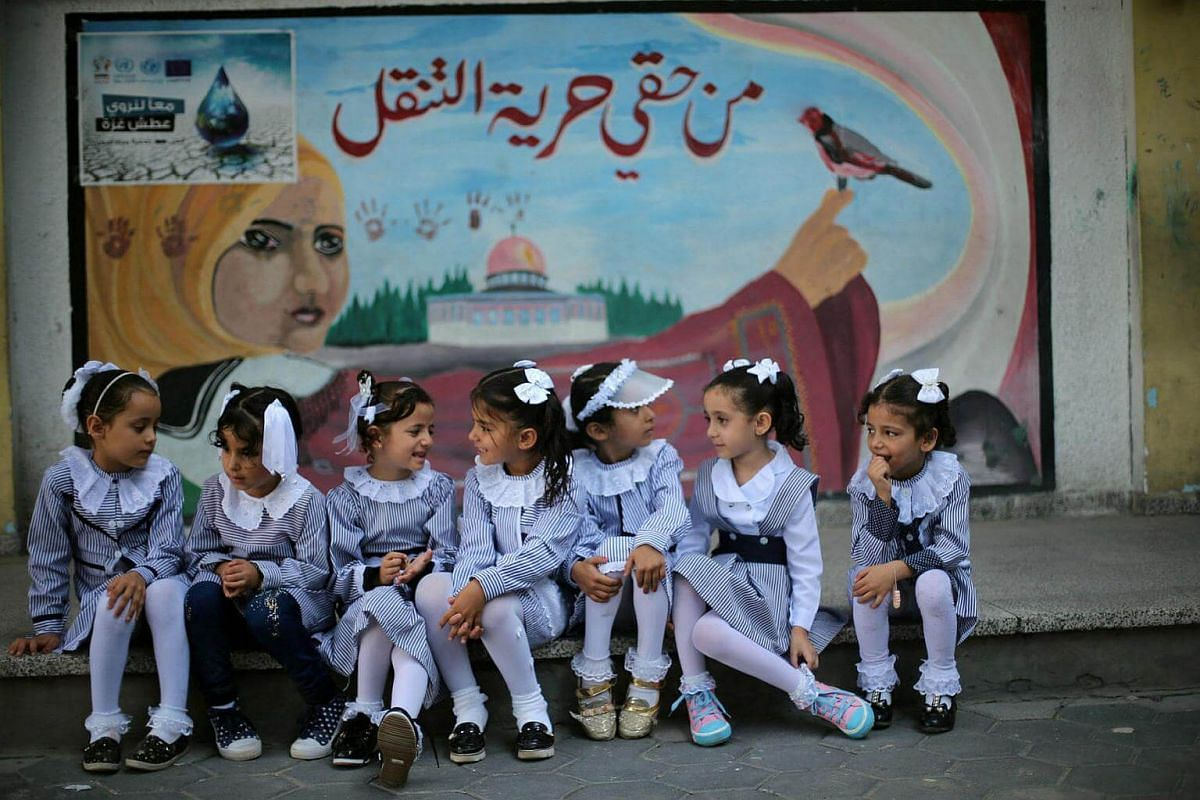 Palestinian schoolgirls sit in front of a mural on the first day of a new school year, at a United Nations-run school in Khan Younis in the southern Gaza Strip on Aug 28, 2016.