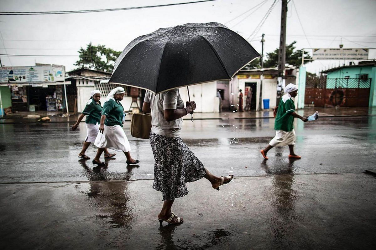 A woman washes her foot with water streaming out of a pipe as catholic nuns leave the St Michel Church in Libreville on Aug 28, 2016.