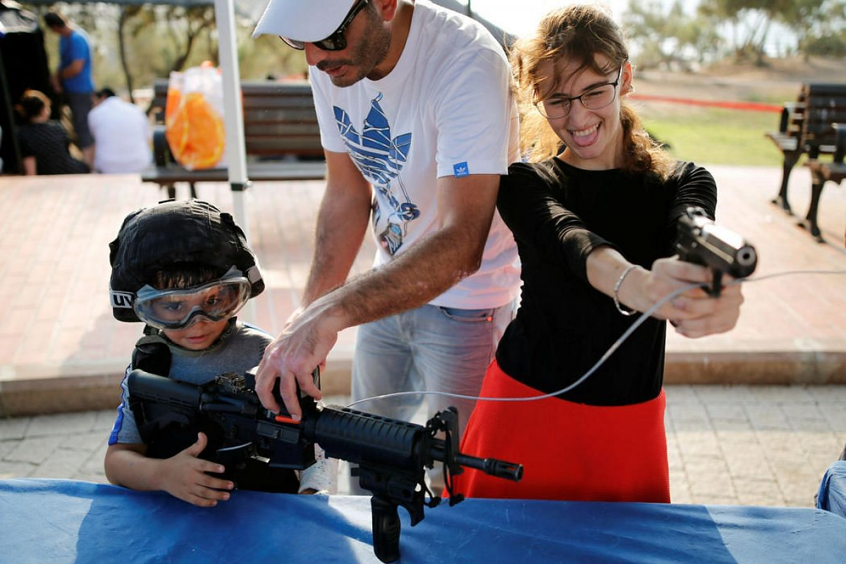 """People play with firearms during an """"open day"""", exhibiting various policing skills and equipment to the public, in the southern Israeli city of Ashdod, on Aug 29."""