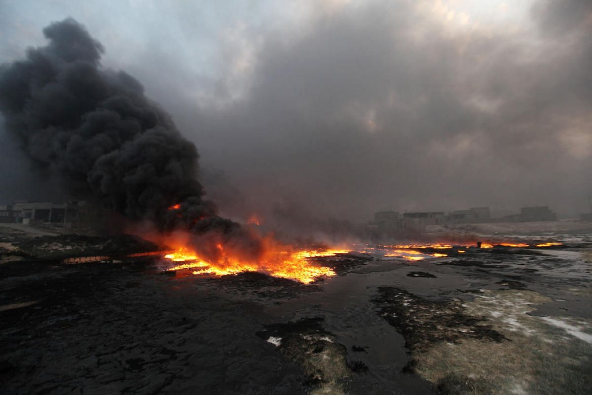 Fire rises from oil wells, set ablaze by Islamic State militants before fleeing the oil-producing region of Qayyara, Iraq, which has been recaptured by Iraqi forces, on Aug 29.