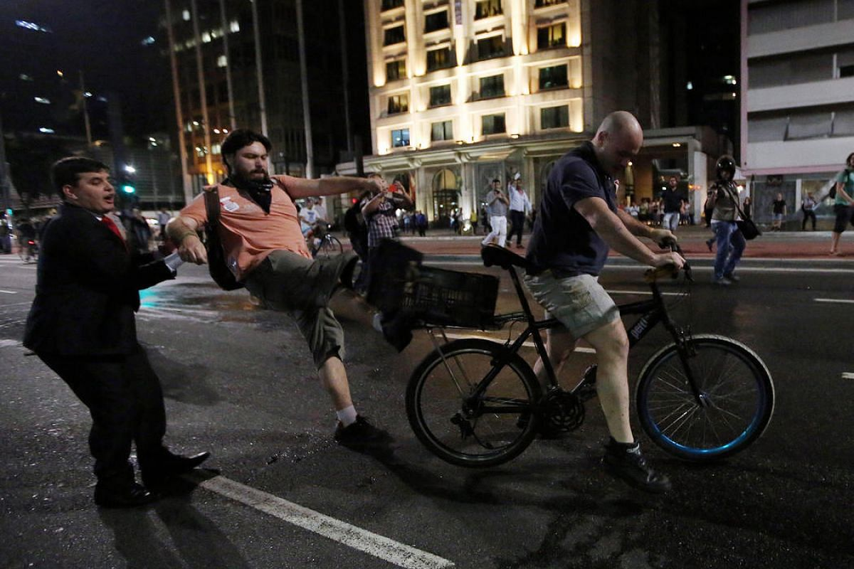 A supporter of Brazil's suspended President Dilma Rousseff kicks the bike of a supporter of interim President Michel Temer during a protest at Paulista avenue in Sao Paulo, Brazil, on Aug 29.
