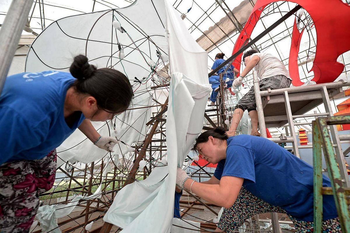 Lantern craftsmen from Sichuan, China, fit fabrics on the 12m steel cable frame of Chang'e's dress for this year's Chinatown Mid-Autumn Festival.