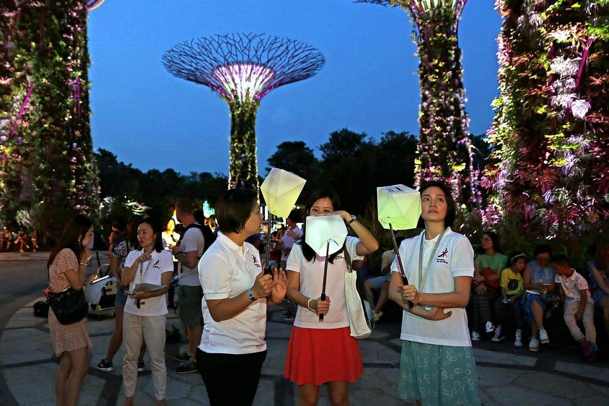 Visitors with lanterns lit up by their phones. The organisers will give out 10,000 of these casings and limited selfie sticks on September 4 at Gardens By The Bay.