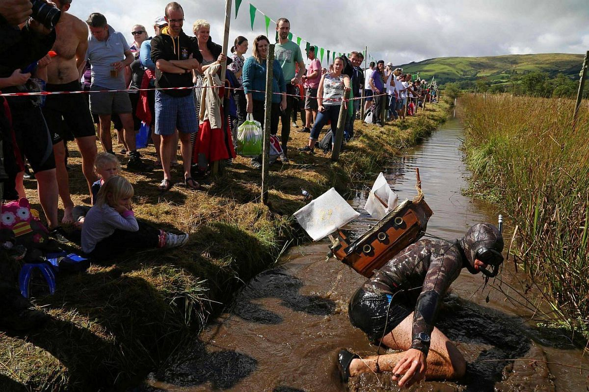 A competitor swims with a model of a galleon on his back as he takes part in the World Bog Snorkelling Championships in Waen Rhydd peat bog at Llanwrtyd Wells in south Wales on Aug 28.