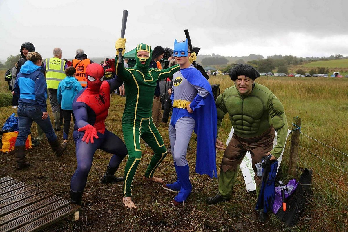 Competitors dressed as superheroes pose for a photograph before they swim the course at the World Bog Snorkelling Championships in Waen Rhydd peat bog at Llanwrtyd Wells, south Wales, on Aug 28.