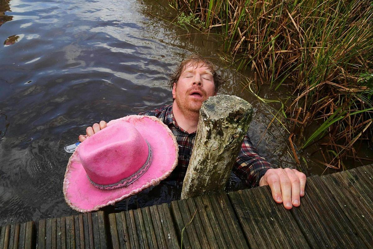 A man dressed as a cowboy lies back exhausted after he swims the course during the World Bog Snorkelling Championships in Waen Rhydd peat bog at Llanwrtyd Wells, south Wales, on Aug 28.