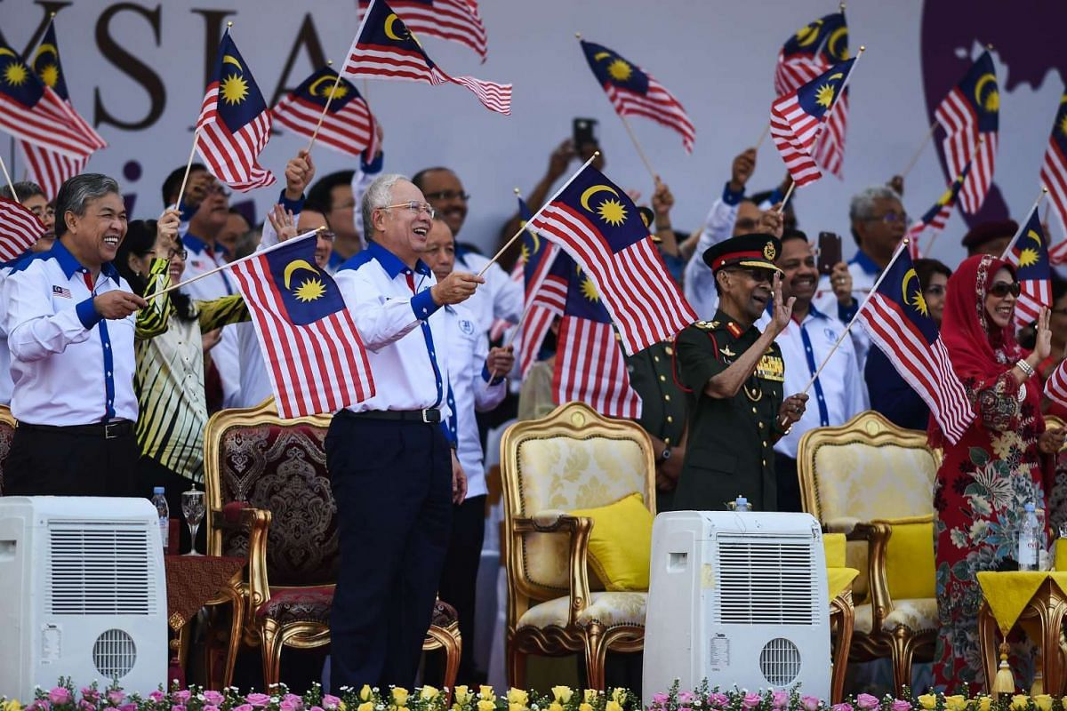 (From front left) Malaysia's Deputy Prime Minister Ahmad Zahid Hamidi, Malaysia's Prime Minister Najib Razak, Malaysia's King Abdul Halim Mu'adzam Shah and Queen Haminah Hamidun wave national flags during the Independence Day celebrations at Independ