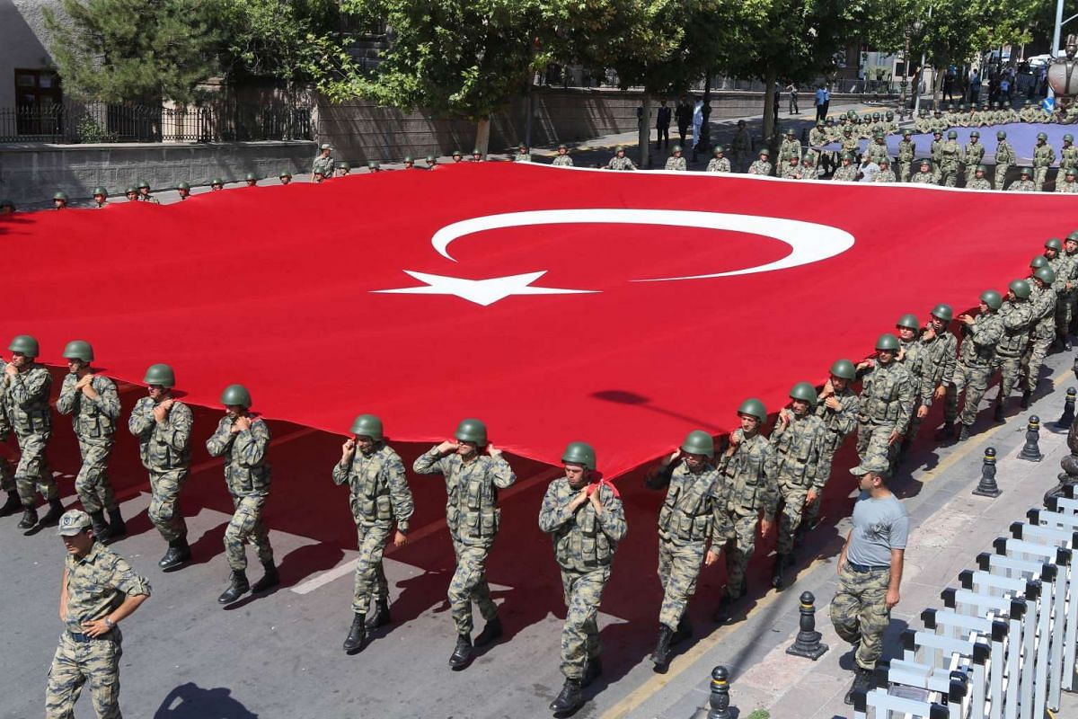 Turkish soldiers carry a giant Turkish flag during a ceremony to mark 94th anniversary of the country's Victory Day in Ankara on Aug 30, 2016.