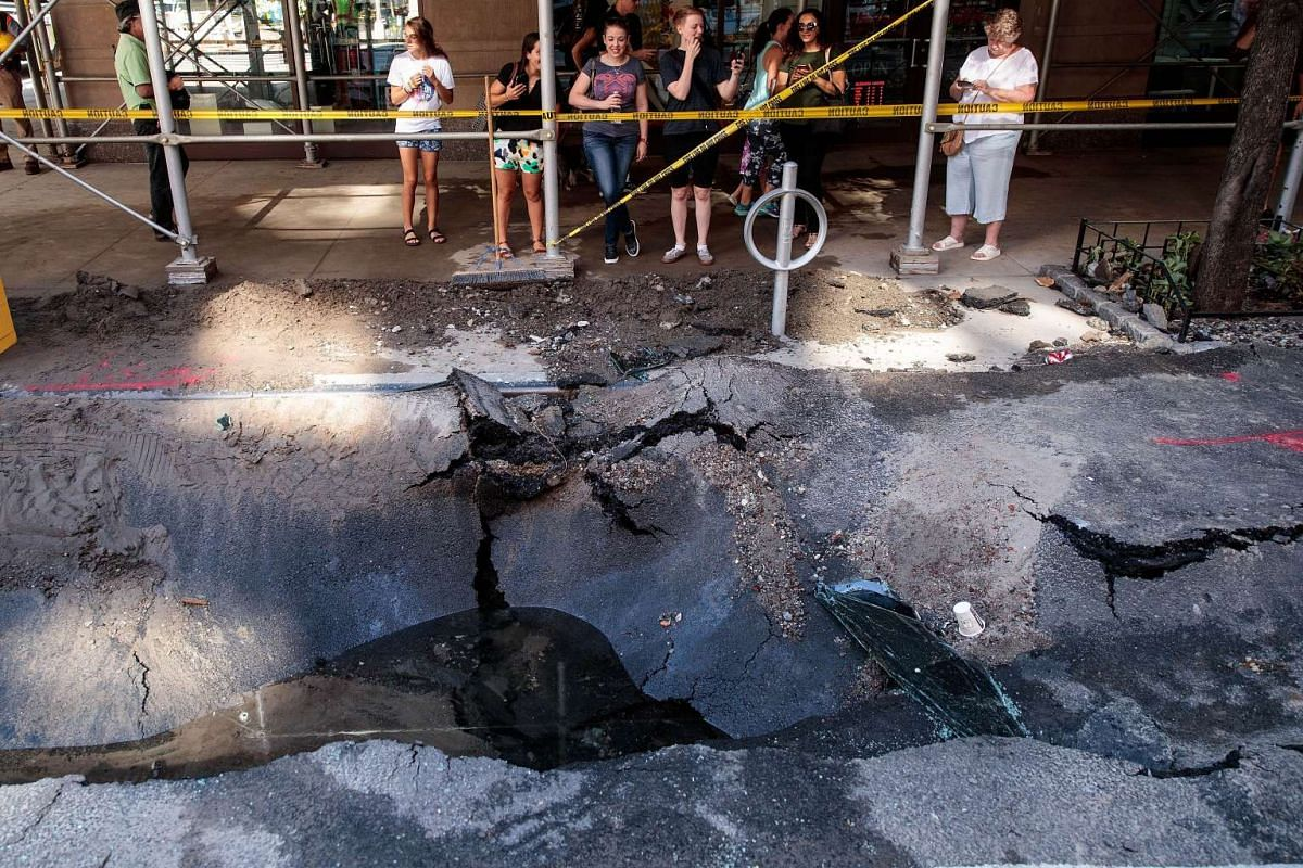 Pedestrians looking at a sinkhole caused by a water main break on Amsterdam Avenue in Manhatten on Aug 30, 2016 in New York City.