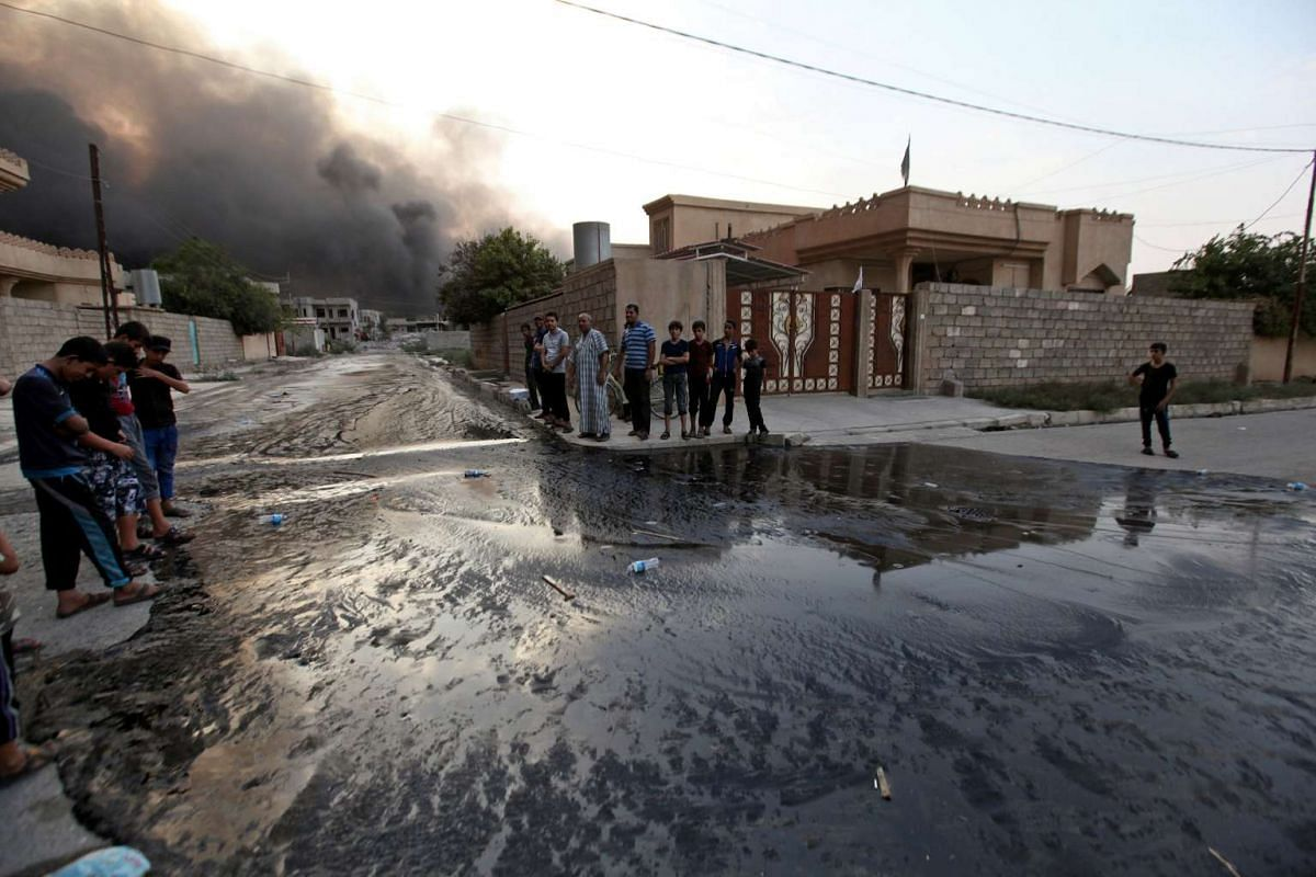 Residents looking at an oil spill from wells, set ablaze by ISIS militants before they fled the oil-producing region of Qayyara in Iraq on Aug 29, 2016.