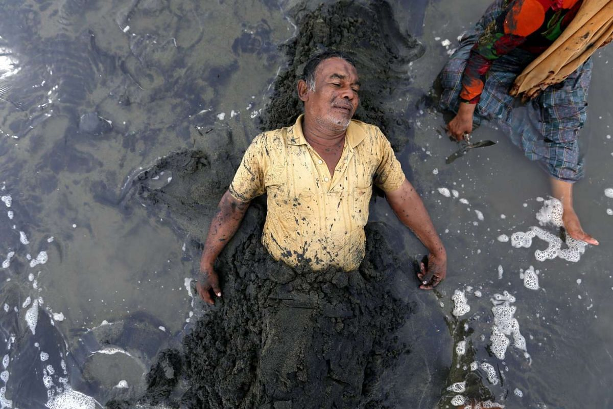 Man who suffered a stroke is buried in black sand as a part of a treatment against a stroke in Syaih Kuala beach, Banda Aceh, Indonesia on Aug 30, 2016.