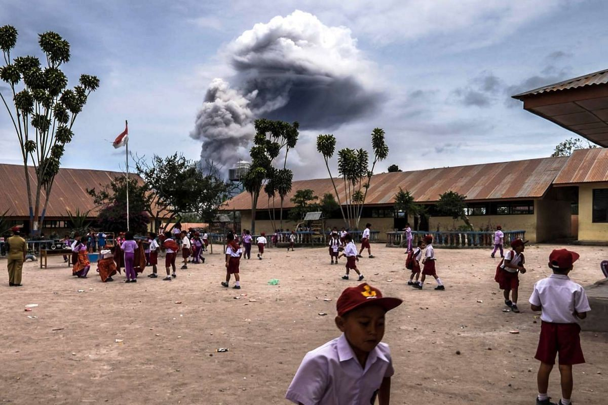 Pupils playing outside their classroom in Gajah Village, Karo, in North Sumatra, Indonesia, while the Mouth Sinabung spew volcanic ash during an eruption on Aug 30, 2016.