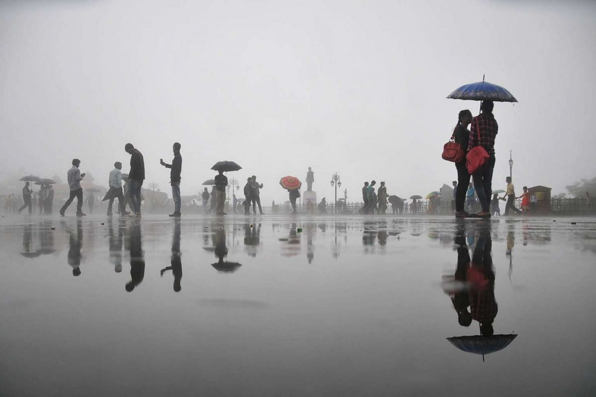Pedestrians sheltering themselves with umbrellas as it rained in Shimla on Aug 30, 2016.