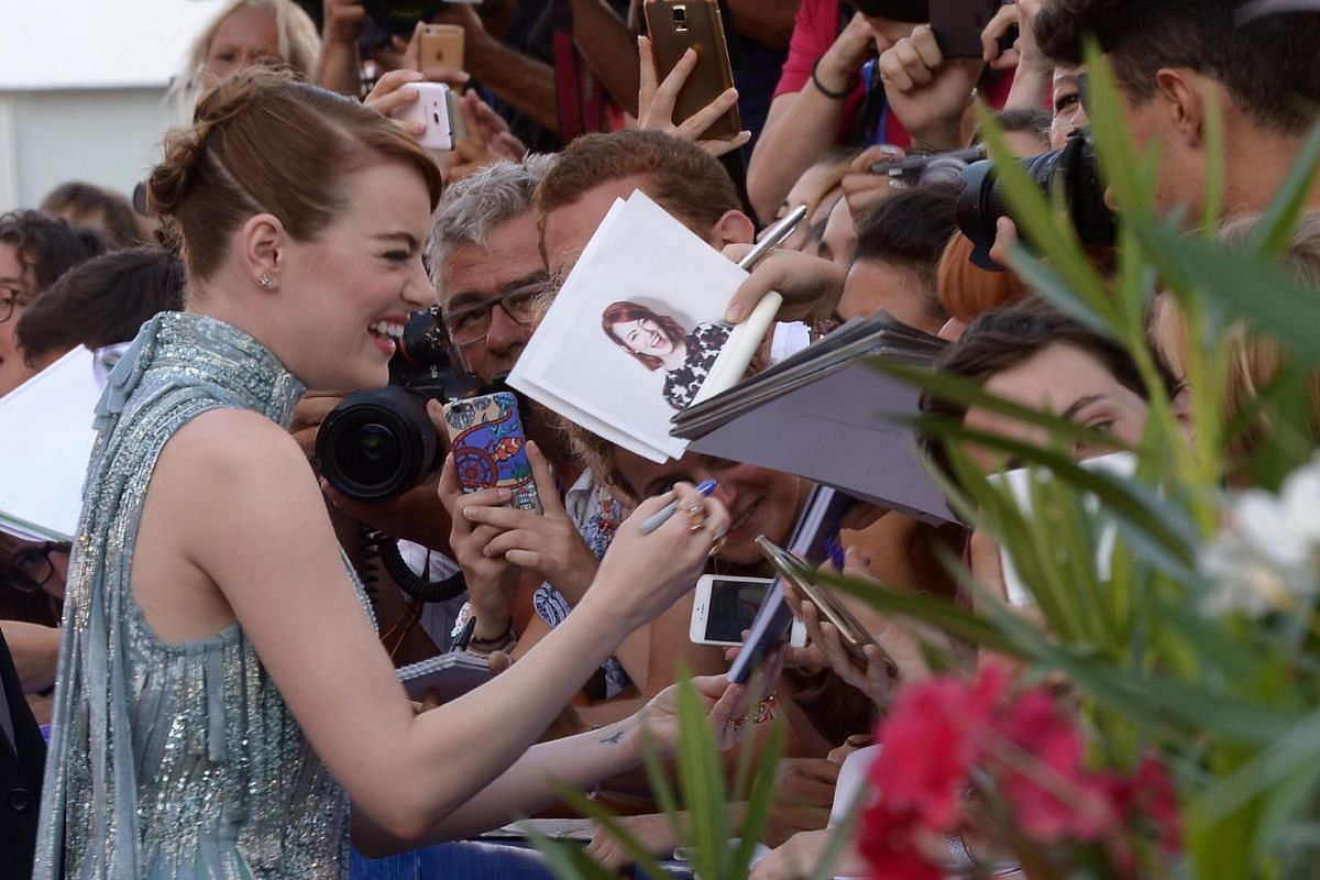 US actress Emma Stone signs autographs on the red carpet as she arrives for the opening ceremony of the 73rd Venice Film Festival, on Aug 31, at Venice Lido.